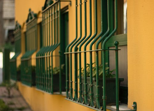 Green Metal Fence on Yellow Concrete Wall