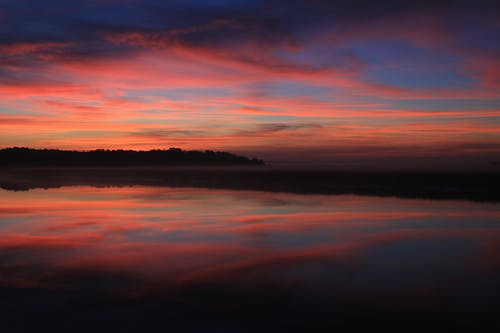 Body of Water Under Blue Red and Yellow Sunset Sky
