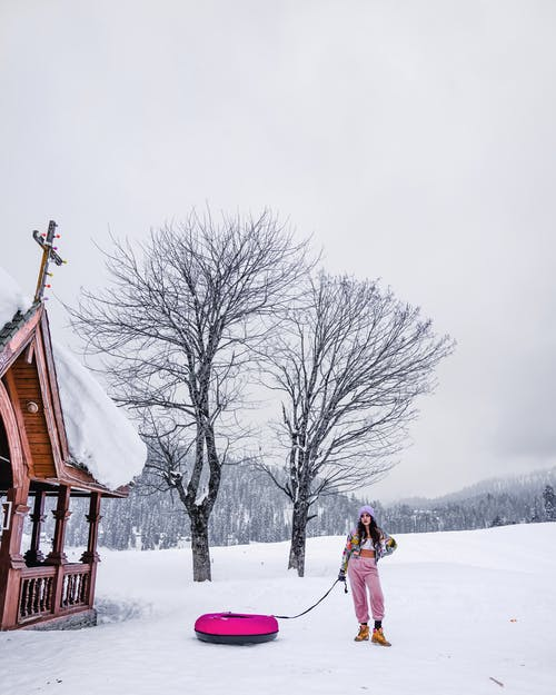 Woman Holding Sled While Standing on Snow