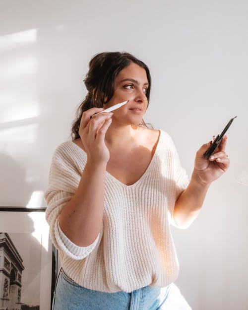 Young woman doing makeup in light room