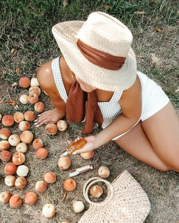 From above of unrecognizable tanned female wearing casual clothes with straw hat sitting on dry grass near woven bag and scattered peaches