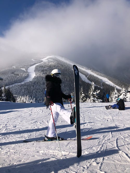 Full body of unrecognizable skier in winter outwear and ski equipment on high snowy slope in daytime