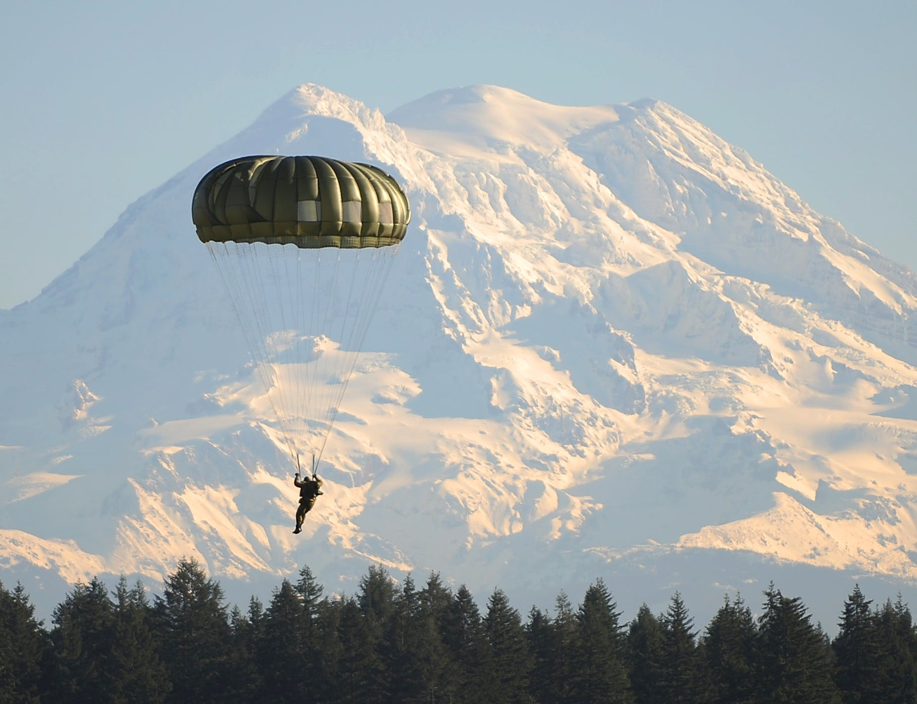 Man Flying on Parachute Near Green Trees