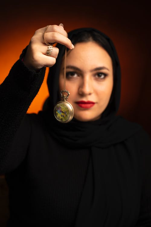 Woman in Black Hijab Holding Clear Glass Ball
