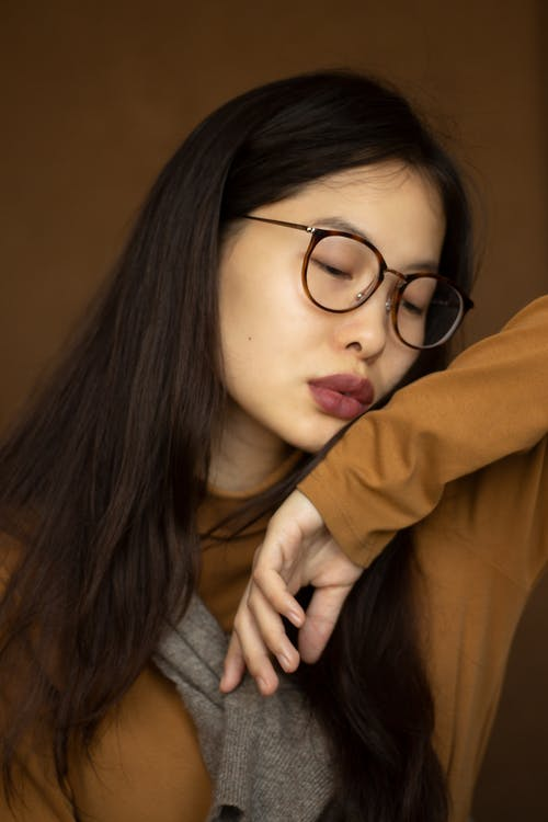 Calm Asian female standing with closed eyes against brown background