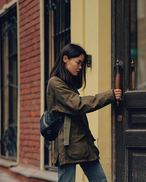 Side view of pensive Asian female in trendy clothes standing on street and opening door of building placed in city in daytime