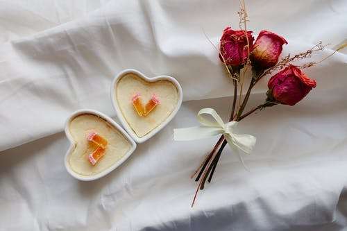 Red Roses Beside A White Heart Shaped Ceramic Plate