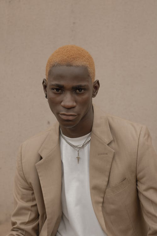 Confident African American male with dyed hair wearing trendy suit and chain looking at camera while standing near wall on street