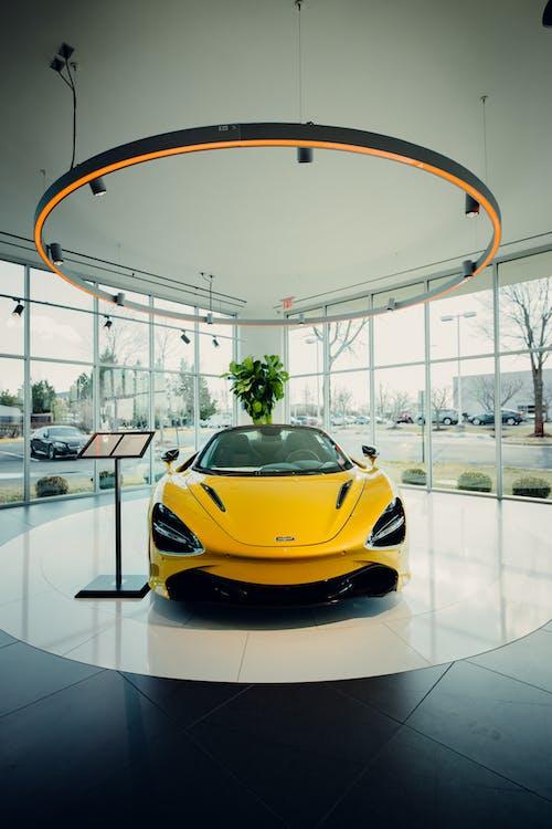 Yellow Luxury Car in Car Dealership Building