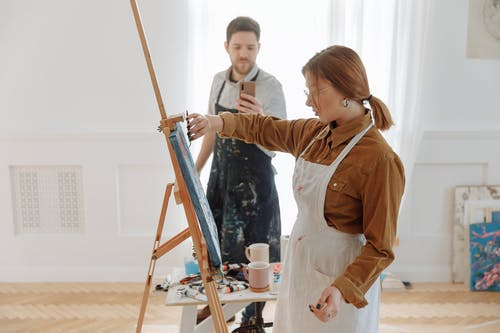 A Man Taking a Picture of a Woman Knife Painting