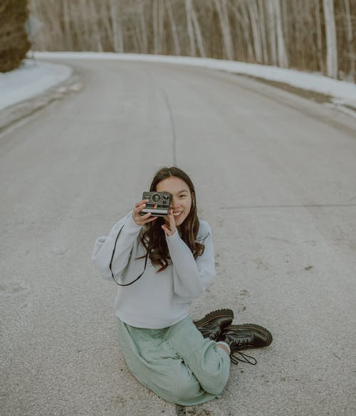 From above of happy young Asian female photographer in trendy outfit smiling and taking pictures on film camera sitting on asphalt road
