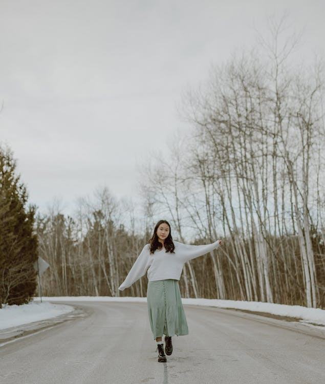 Full body of stylish young Asian female millennial with dark hair in trendy sweater and skirt walking along asphalt road with outstretched arms against cloudy sky