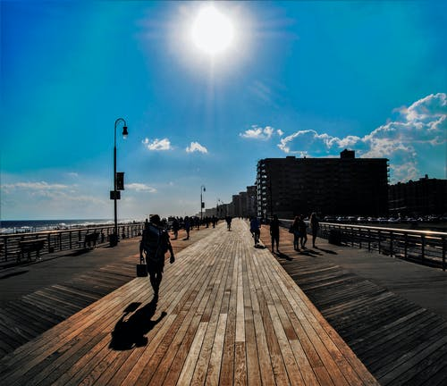 People Walking on Pathway Under Blue Sky during Daytime