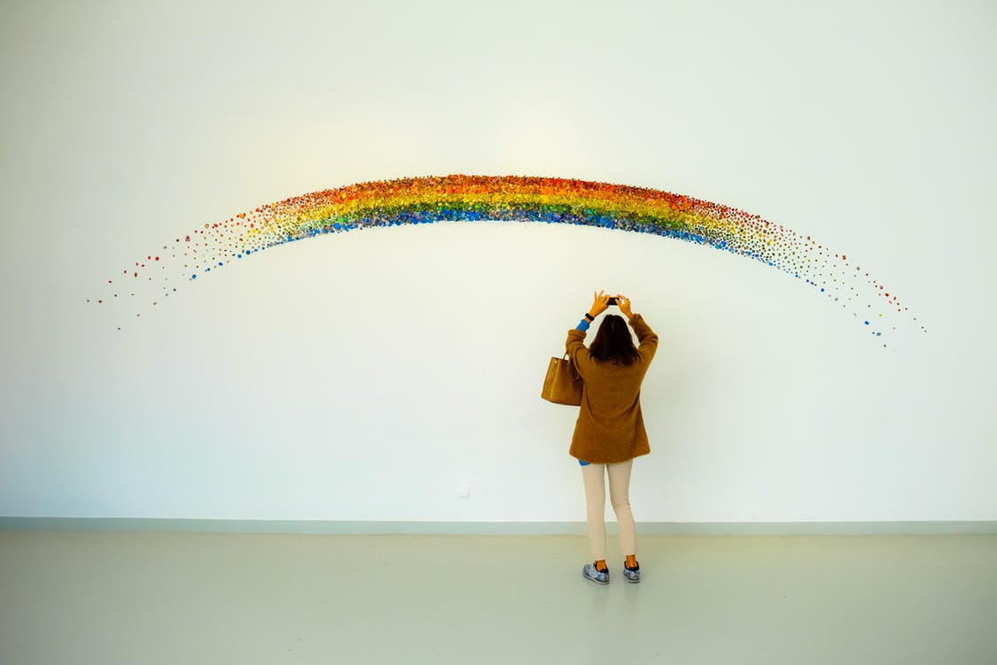 Woman Wearing Brown Top and Beige Leggings Taking Picture Rainbow Painted Wall