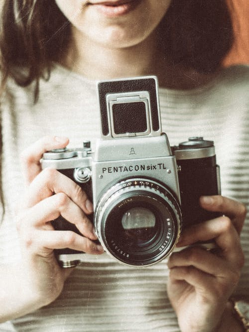 Crop unrecognizable young female photographer with long dark hair in casual clothes taking pictures on retro camera