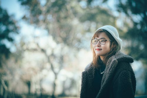 Selective Focus Photo of a Woman with Eyeglasses Wearing a Fur Coat