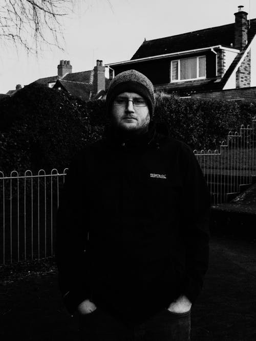 Man in Black Jacket Standing Near Fence