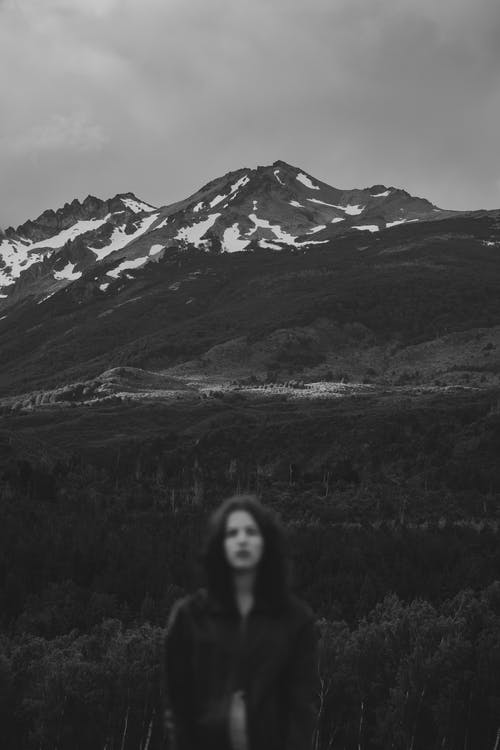 Black and white of unrecognizable young female tourist with long dark hair recreating in mountainous valley amidst lush trees under overcast sky