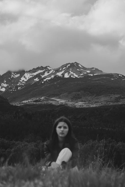 Black and white of calm young female millennial in casual clothes resting on grassy meadow during holidays in mountainous countryside on cloudy day