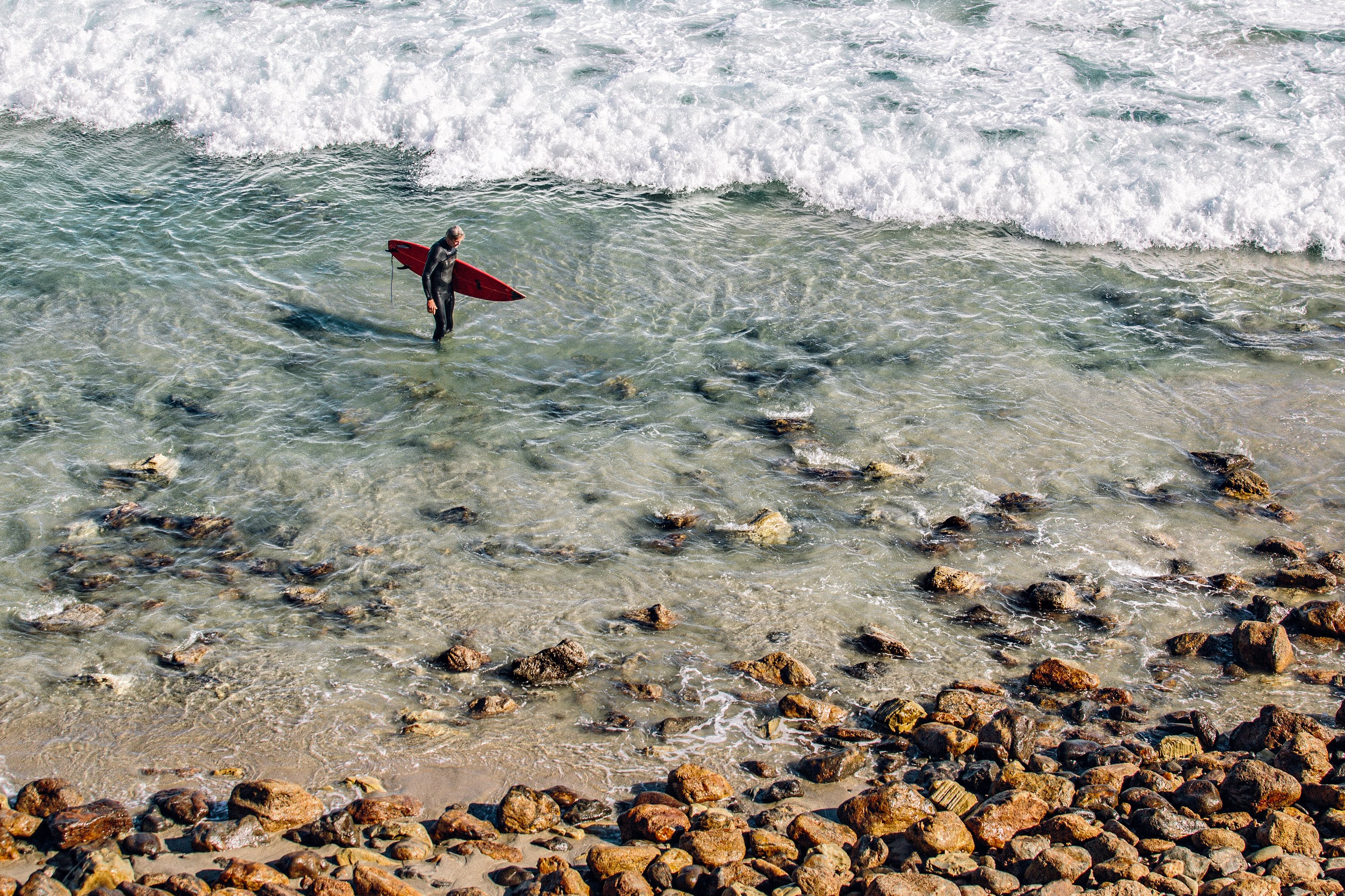 Person Holding Red Surfing Board in Clear Water Near Brown Stone during Daytime