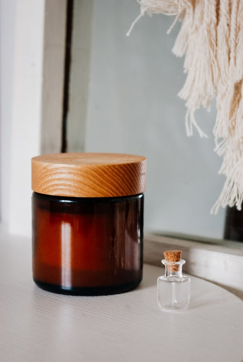 Cosmetic skin care product in glass jar and small bottle of perfume arranged on white table in room