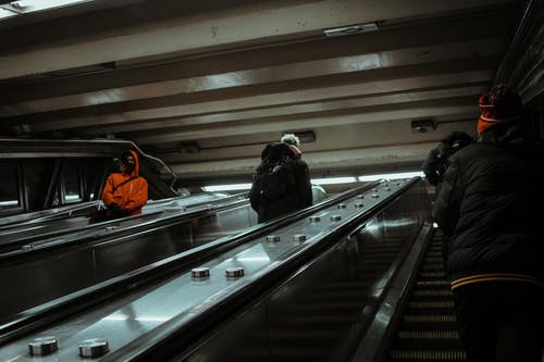 Crowd of people in warm outerwear standing on steps while riding contemporary escalator with metal handrails in modern subway station