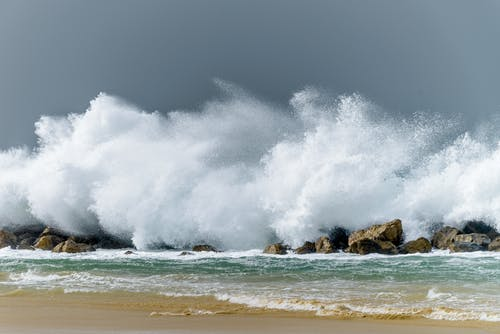 Waves splashing in stormy ocean near boulders and sandy beach
