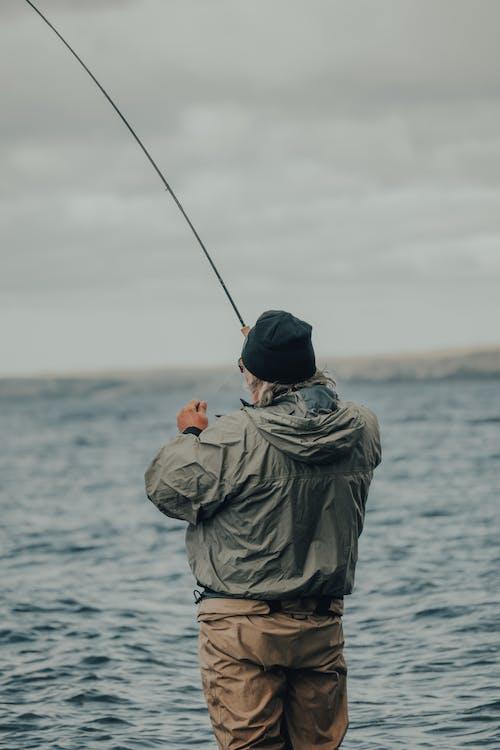 Man in Green Jacket Fishing on Sea