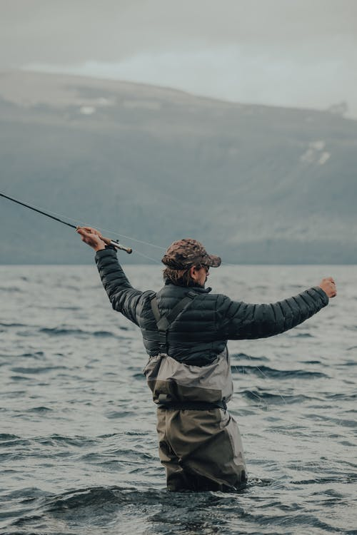 Man in Black Jacket and Brown Pants Holding Black Fishing Rod