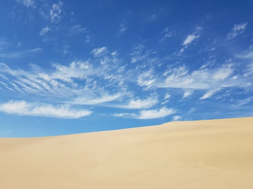 Amazing scenery of sand dunes in uninhabited desert against bright blue sky in sunny day