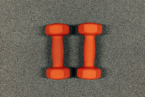 Pair Of Orange Dumbbells On Gray Surface