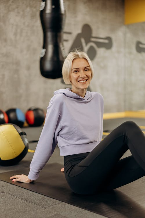 Smiling Woman Sitting On A Mat