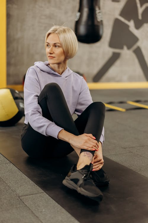A Sporty Woman Sitting On A Mat