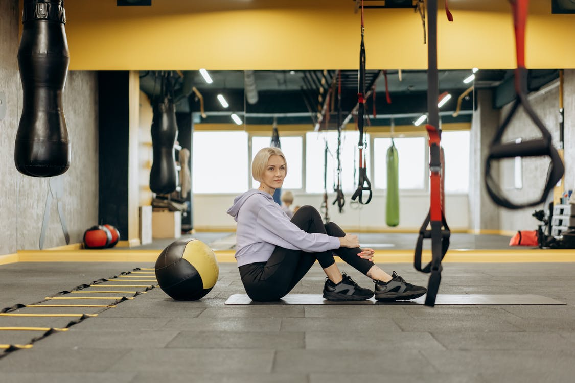 Woman Sitting On A Mat Inside The Gym