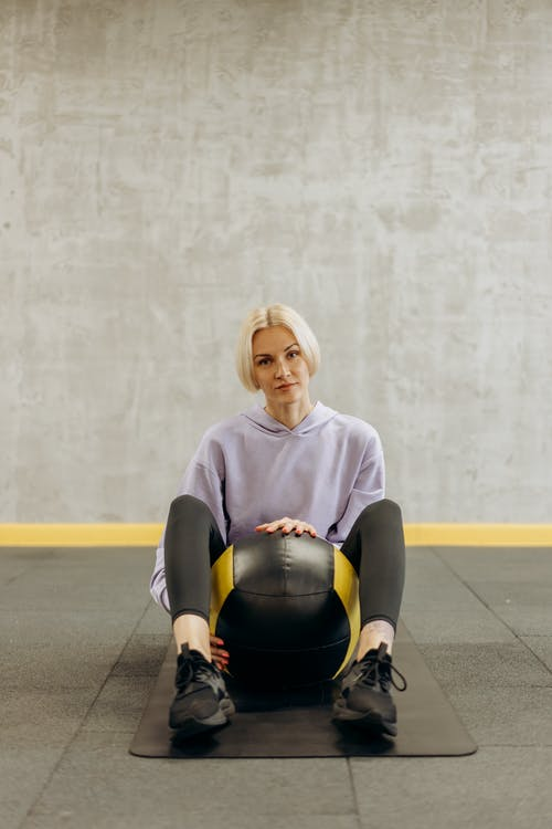 Woman Sitting With A Ball Between Her Legs