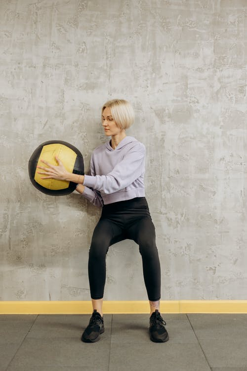 Woman Leaning On Wall With A Ball