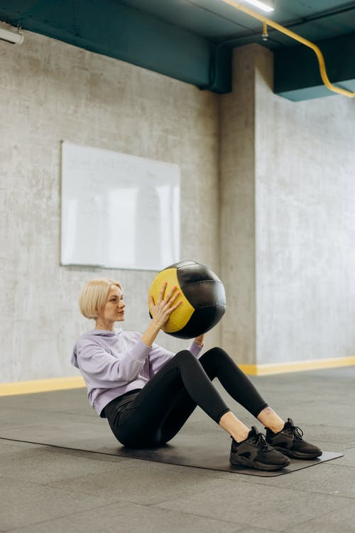 Woman Sitting On A Mat With A Ball