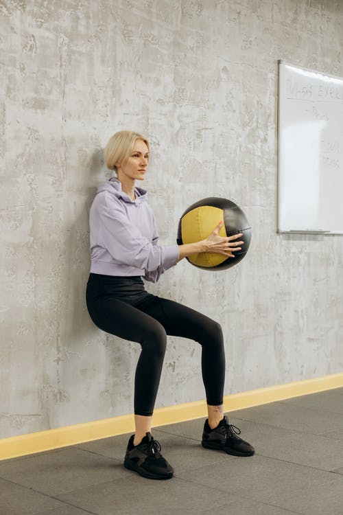 Woman Leaning On The Wall With A Ball