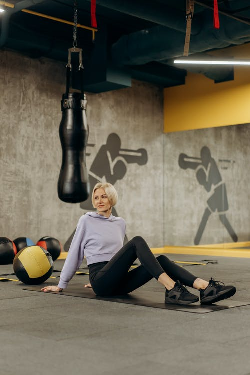Woman Lying On A Mat Beside An Exercise Ball