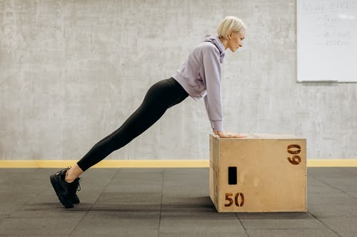 Woman Standing In A Bending Position On A Box