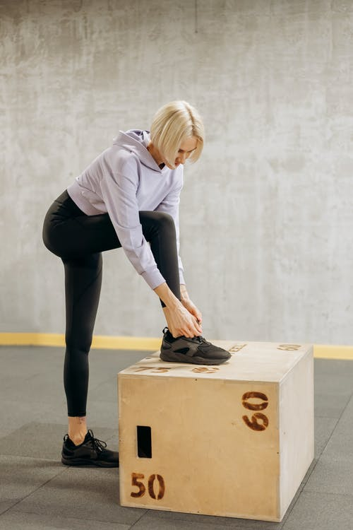 Woman Fixing On Her Black Sneakers
