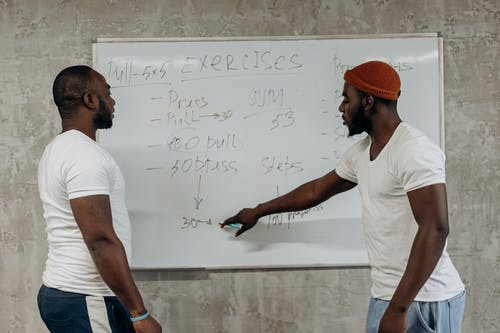 Two Men Looking At A Workout Schedule On A Whiteboard