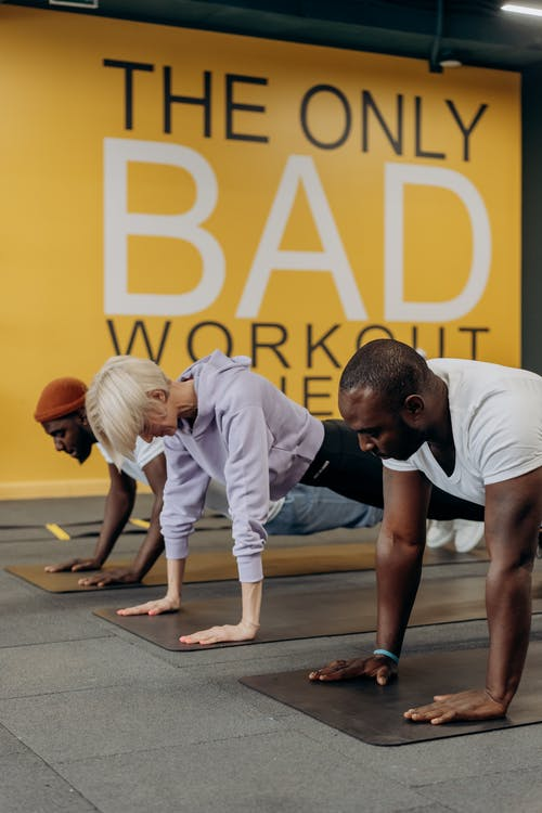 Two Men And Woman Doing Push Up