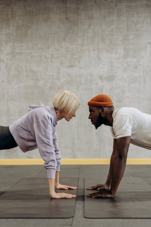 Man And Woman Doing Push Up Face To Face