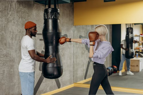 Man in White Shirt and Black Pants Holding A Punching Bag