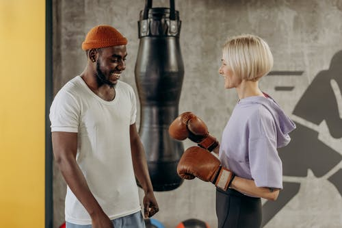 Woman Wearing A Boxing Gloves With Trainer Beside Her