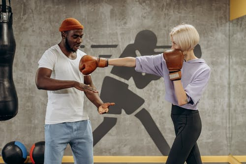 Man Training Woman In Boxing
