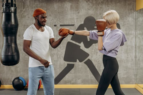 Man Training A Woman How To Punch In Boxing