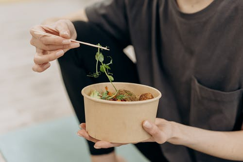 Person Holding White Ceramic Bowl With Green Leaf