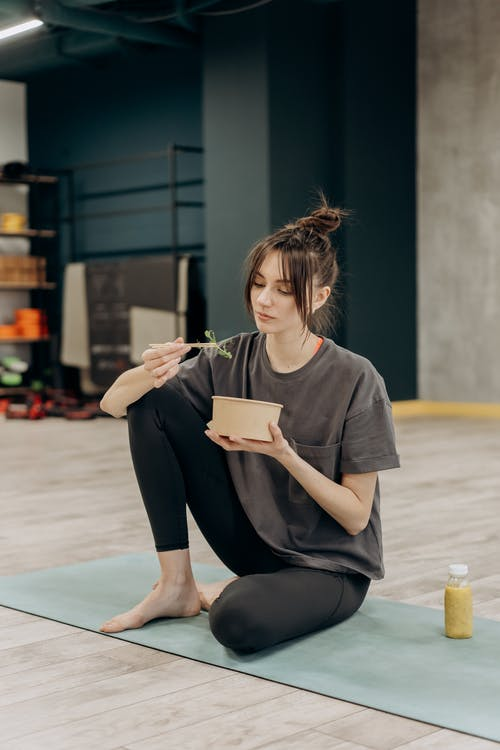 Woman in Gray T-shirt and Black Leggings Sitting on Blue Yoga Mat